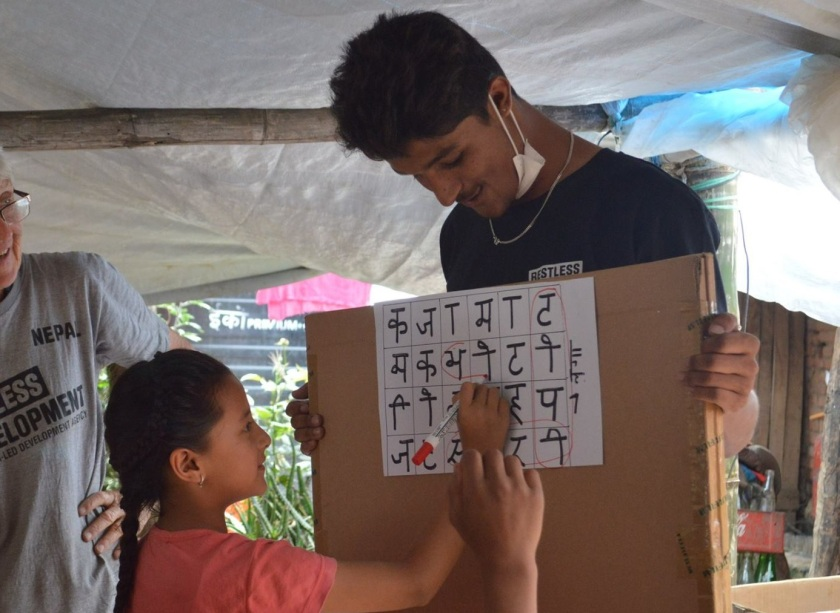 Young Nepalese volunteer supporting children