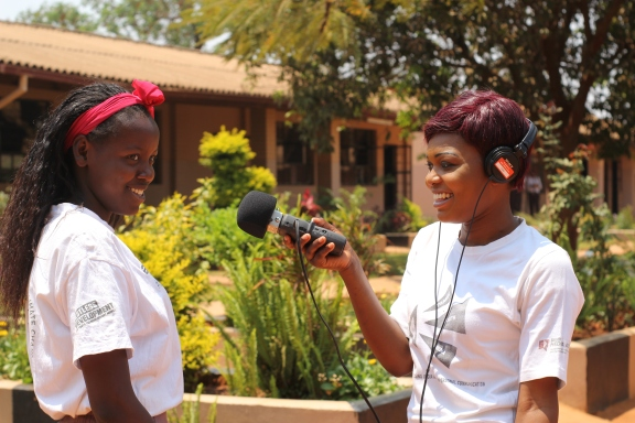 """""""Come on - let's get a photo of us!"""" Community journalist Purity, 20, interviewing her friend and fellow volunteer as part of the Tikambe project. Tikambe! (Let's Talk!) is a joint BBC Media Action and Restless Development project in Zambia using TV, radio and online media to help young people look after their sexual health and improve their knowledge of their reproductive rights. (PC Restless Development/ Gemma Munday)"""