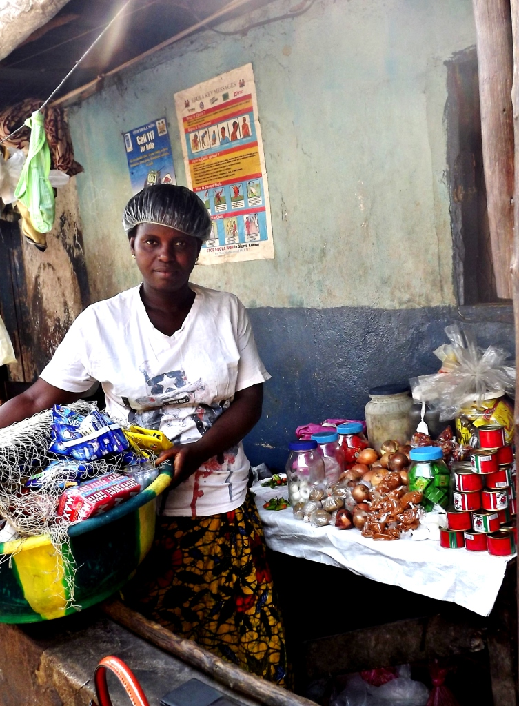 Hawanatu Koroma, a member of a REFLECT savings group run by Restless Development, displays products from her shop in Kolvart slum. Hawanatu saved Le50,000 through the group, and was able to take a loan to start her business. Since 2014 she has paid back the loan, and is still saving now with the group, allowing her to contribute to her child's education, and pay healthcare costs within the community.